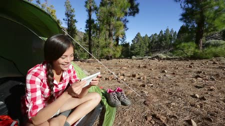 aktywność : Tablet computer pc used by camping woman hiker in tent at campsite. Girl camper using tablet relaxing enjoying active outdoors lifestyle.