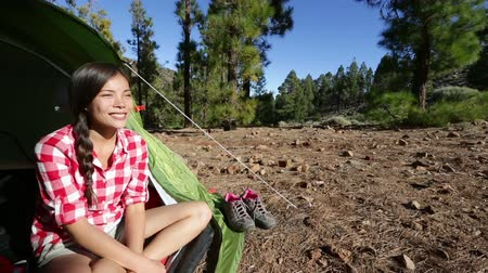 etkinlik : Camper woman camping sitting relaxing enjoying view at campsite in tent in forest. Beautiful young smiling happy mixed race Asian Caucasian female model in outdoor activity. Stok Video
