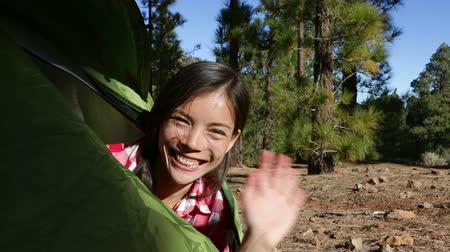 good : Woman camping waving hello from tent smiling happy outdoors in forest. Happy girl saying hello and goodbye closing tent. Smiling mixed race Asian Caucasian girl saying hi looking at camera. Stock Footage