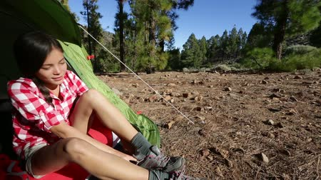 bota : Camping woman tying hiking shoes walking from tent at campsite going on hike in forest. Beautiful young smiling happy mixed race Asian Caucasian female hiker model in outdoor activity.