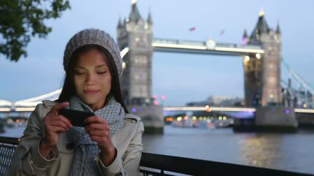 utazó : Asian tourist in London taking self-portrait photo smiling happy showing victory v hand sign with Tower Bridge in background. Travel and tourism concept with beautiful girl traveling in London, England.
