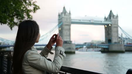 mosty : London woman tourist taking photo on Tower Bridge with mobile smart phone camera. Girl enjoying view over the River Thames, London, England, Great Britain. United Kingdom tourism concept.