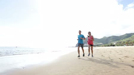 estilo de vida saudável : Runners running on beach. Jogging couple training on beach in full body length living healthy active lifestyle. Asian runner woman and fit male fitness athlete on run. Vídeos