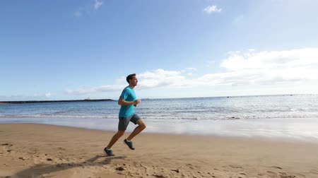 kimerül : Running sport man jogging on beach in full body length training outdoors for marathon run as part of active healthy lifestyle outside. Fit male fitness model exercising.