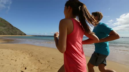 kimerül : Running couple. Runners jogging on beach training together. Man and woman joggers exercising outdoors.