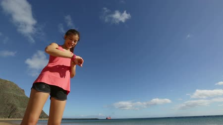 oran : Runner woman using heart rate monitor stopwatch starting watch going running on beach. Sport fitness girl exercising and training outside under blue sky by the sea.