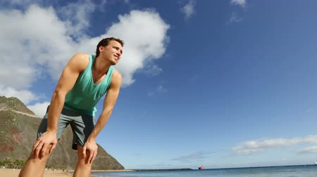 yorgunluk : Running athlete man jogging stopping resting tired and sweating after jogging on beach. Runner training for healthy lifestyle. Active young sport man exercising working out on tropical summer beach. Stok Video