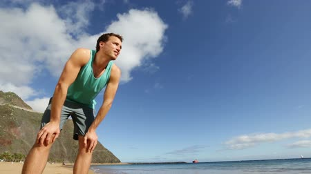 kocogó : Athlete resting tired sweating starting running on beach jogging training for healthy lifestyle. Active young sport man exercising working out on tropical summer beach. Stock mozgókép