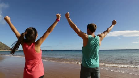 Happy couple cheering raising arms celebrating on beach, excited and joyful in celebration. Fit fitness sport running athletes, Asian woman and Caucasian man having fun on beach together. Стоковые видеозаписи