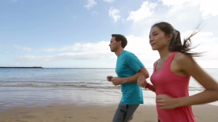 jogging : Couple running outdoors on beach. Woman and man runners jogging together outside in full body length. Stock Footage