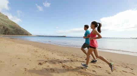 kimerül : Running couple jogging on beach exercising and jogging training. Runners working out on summer beach.