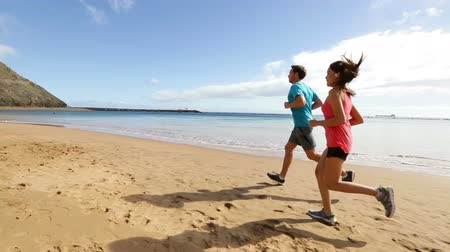 kimerül : People running on beach training and jogging. Runners couple working out exercising together. Asian woman model and fit Caucasian fitness runner man. Stock mozgókép