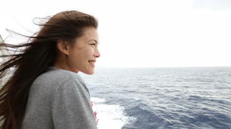 utazó : Cruise ship woman on boat in happy smiling looking at camera and looking away. Young woman traveling on vacation travel sailing on open sea ocean. Mixed race Asian Caucasian woman. Stock mozgókép