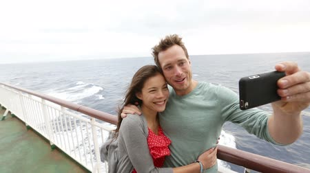 társkereső : Cruise ship couple taking selfie self portrait photo romantic. Happy lovers, woman and man traveling on vacation travel sailing on open sea ocean enjoying romance. Young Asian woman and Caucasian man.