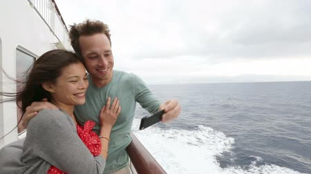 медовый месяц : Cruise ship couple taking selfie self portrait photo romantic. Happy lovers, woman and man traveling on vacation travel sailing on open sea ocean enjoying romance. Young Asian woman and Caucasian man.