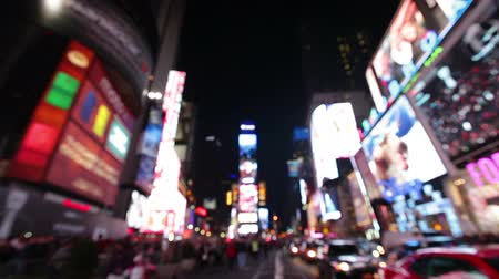 light : New York City, Times Square, Manhattan background out of focus with blurry unfocused city lights and billboards. City at night with cars and pedestrians people walking.