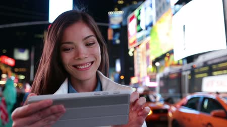 eszköz : Tablet computer - woman using app in New York City, Time Square, Manhattan. Girl tourist or New Yorker on small tablet pc at night. Lifestyle video with beautiful multiracial woman in her 20s.