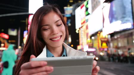 таблетка : App - woman using tablet apps in New York City, Time Square, Manhattan. Girl tourist or New Yorker on small tablet pc at night. Lifestyle video with beautiful multiracial woman in her 20s. Стоковые видеозаписи