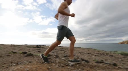 buty sportowe : Sport runner running man on cross country trail run. Fit male runner exercise training beautiful ocean nature landscape.