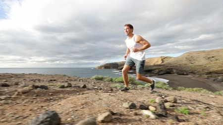 jogging : Sport runner trail running cross country. Fit male runner exercise training beautiful ocean nature landscape on Tenerife, Canary Islands, Spain.