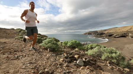 шорты : Trail running sport runner athlete jogging in cross country run. Fit male runner exercise training beautiful ocean nature landscape on Tenerife, Canary Islands, Spain.
