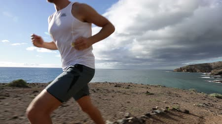 running man : Running sport man in cross country trail run. Fit male runner exercise training beautiful ocean nature landscape on Tenerife, Canary Islands, Spain. Stock Footage