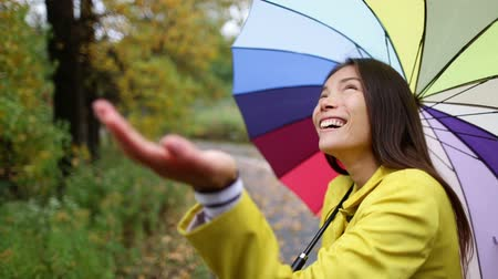andar : Autumn  fall woman happy in rain with umbrella. Female model looking up at clearing sky joyful on rainy fall day wearing yellow raincoat outside in nature forest by lake. Multi-ethnic Asian girl. Vídeos