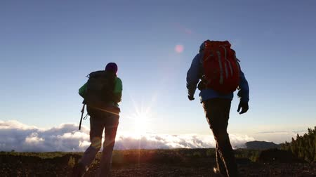 peak : Hikers reaching summit cheering happy at sunset. Hiking couple walking in mountain reaching top.