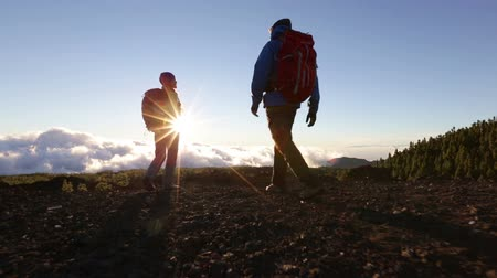 peak : Hiking people reaching summit top giving high five at mountain top at sunset. Happy hiker couple.