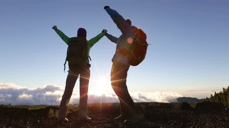 alpy : Cheering celebrating happy people at hike excited with arms raised op in fun cheerful celebration at sunset.