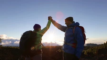 Hikers - cheering happy people giving high five outdoors on trekking hike. Happy hiking couple celebrating cheering have reached summit mountain top. Стоковые видеозаписи