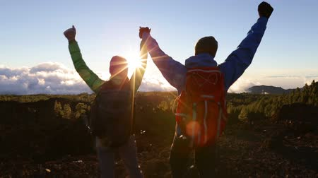 Freedom - Happy couple cheering and celebrating running. Hiking man and woman raising arms excited in celebration outdoors. Hikers at sunset in mountain enjoying mountain top summit and success.