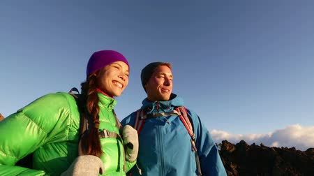 People watching sunset hiking laughing taking together resting enjoying break after hike in mountain. Sporty active young multiracial couple living healthy outdoors lifestyle together. Стоковые видеозаписи