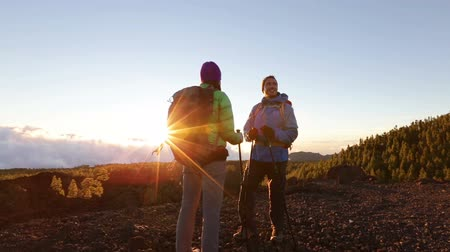 наслаждаясь : Hiking adventure people on Tenerife, Canaries. Couple standing talking. Couple enjoying sunset view above the clouds on trek. Video of young woman and man in nature wearing hiking backs and sticks.