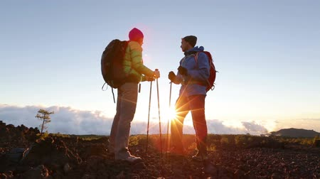 hiking : Hiking adventure healthy outdoors people standing talking. Couple enjoying sunset view above the clouds on trek. Video of young woman and man in nature wearing hiking backpacks and sticks.
