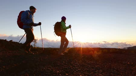 поход : Hiking couple - hikers trekking at sunset. Hiker man and woman in beautiful mountain nature landscape. Woman and man hikers walking during hike on volcano Teide, Tenerife, Canary Islands, Spain. Стоковые видеозаписи