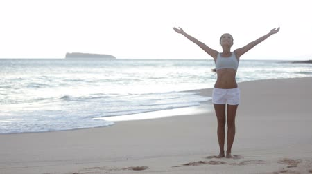 serbest : Free woman enjoying freedom feeling happy at beach at sunset. Beautiful serene relaxing woman in pure happiness and elated enjoyment with arms raised outstretched up on Makena beach, Maui, Hawaii, USA