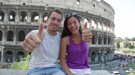 utazó : Travel couple waving hello hands by Colosseum, Rome, Italy. Smiling young romantic couple traveling in Europe looking at camera smiling in front of Coliseum. Caucasian man and Asian woman.