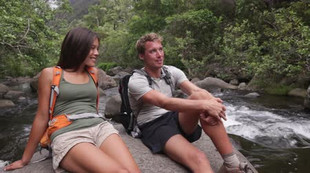 etkinlik : Hikers couple relaxing by river enjoying outdoor activity wearing backpacks sitting down. Woman and man hiker looking with smiling happy. Healthy lifestyle image.