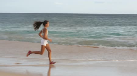 kardiyoloji : Running woman healthy lifestyle jogging on beach. Female runner training exercising outdoors. Happy fit jogger living healthy lifestyle training outside. Fit mixed race Asian Caucasian fitness girl.