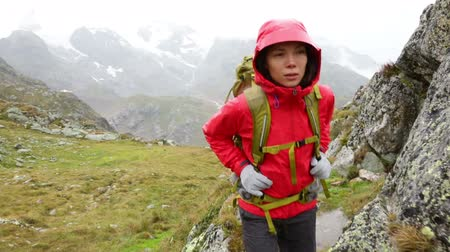 поход : Hiking - woman hiker backpack trekking in rain living healthy active lifestyle. Hiker girl walking on hike in beautiful mountain nature landscape while raining in Swiss alps, Switzerland. Стоковые видеозаписи