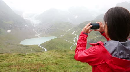 obrázky : Woman taking picture with smart phone in Swiss alps. Female hiker using smartphone app to take photos in mountain in Switzerland.