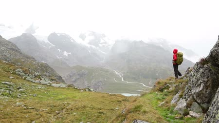 поход : Hiking - hiker woman on trek with backpack in rain living healthy active lifestyle. Hiker girl walking away on hike in beautiful mountain nature landscape while raining in Swiss alps, Switzerland.