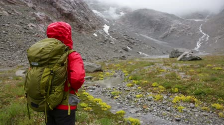 поход : Trekking woman hiking on hike with backpack in rain living healthy active lifestyle. Hiker girl walking away on hike in beautiful mountain nature landscape while raining in Swiss alps, Switzerland.