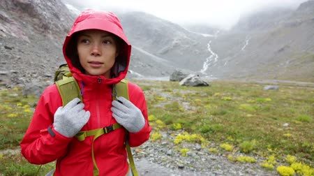 поход : Hiker woman hiking with backpack in rain on trek living healthy active lifestyle. Hiker girl walking away on hike in beautiful mountain nature landscape while raining in Swiss alps, Switzerland. Стоковые видеозаписи