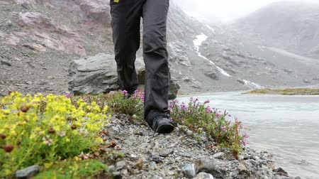 calçados : Hiking - woman hiker walking in nature. Closeup of hiking shoes boots trekking by river outdoors in rain. Female and trekking boots outdoors in Swiss alps, Switzerland.