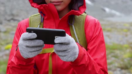 tecido : Smart phone woman texting sms using app on smartphone with touchscreen gloves. Closeup of mobile phone and female hands outside in nature in rain. Girl with glove of conductive fabric for touch screen