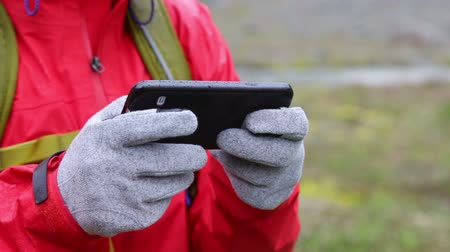tecido : Woman sms texting using app on smart phone with touchscreen gloves. Closeup of smartphone and female hands outside in nature in rain. Girl wearing glove of conductive fabric for touch screen.