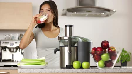 meyve suyu : Apple juice - woman juicing apples and vegetables and drinking it fresh at home in kitchen giving thumbs up. Juice machine and healthy eating happy woman making green vegetable and fruit juice.