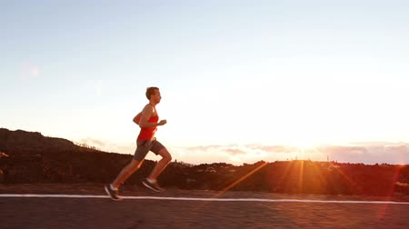 perfil : Running runner man athlete training outdoors exercising on mountain road at sunset in amazing landscape nature. Fit handsome athletic male working out for marathon run outside in summer.